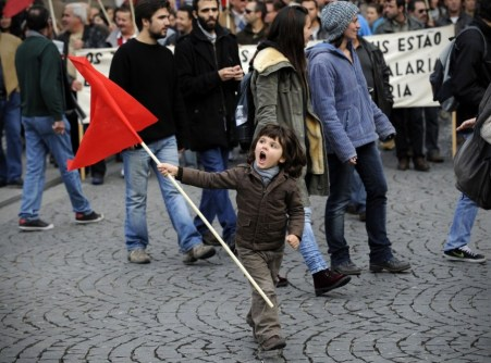 waves-a-red-flag-and-joins-her-elders-at-a-general-strike-in-porto-portugal-to-protest-austerity-measures-planned-by-the-government-on-november-14-2012